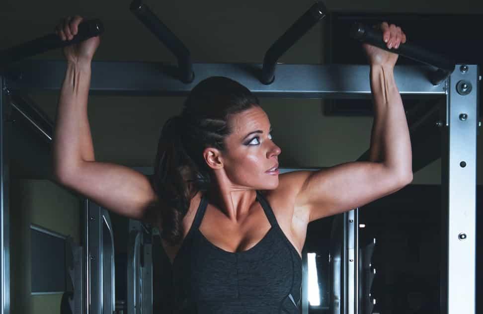 mujer haciendo dominadas por tener entrenador personal