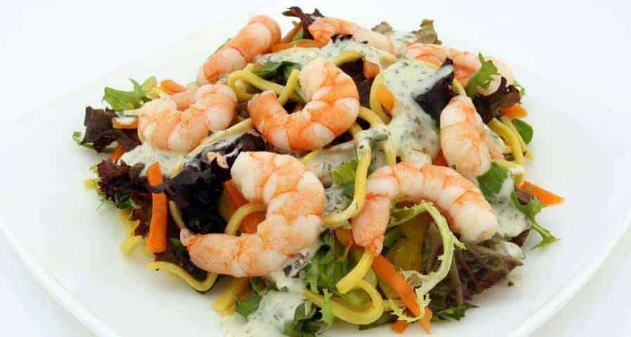 plato saludable de ensalada, pasta y gambas. Comer bien para el entrenamiento